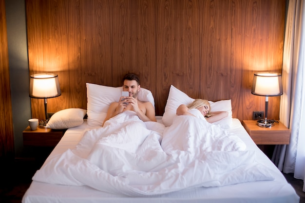Man using mobile phone while wife sleeping in the bed