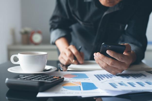 Человек с помощью мобильного телефона во время работы над деловым документом в офисе