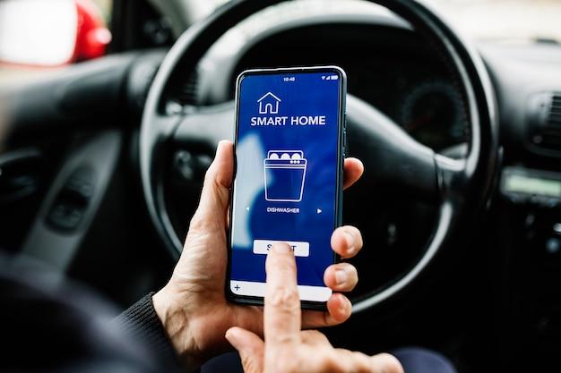 Человек использует мобильный телефон с приложением для умного дома на экране при удаленном программировании посудомоечной машины