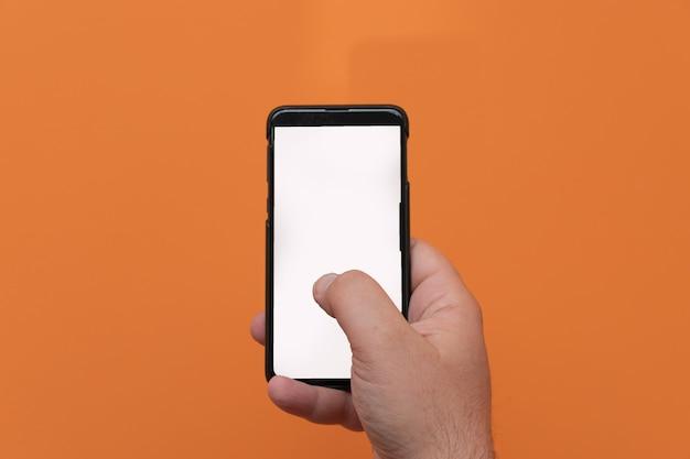 オレンジ色の背景に分離された携帯電話のスマートフォンを使用して男。