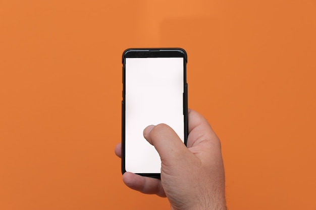 Man using mobile smart phone isolated on orange background.