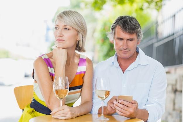 Человек, используя мобильный телефон с женщиной в кафе