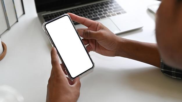 Человек используя мобильный телефон модель-макета на столе офиса с дисплеем пути клиппирования.