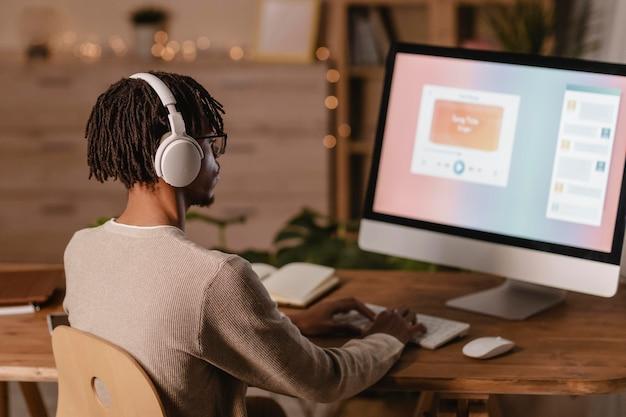 現代のコンピューターとヘッドフォンを使用している男