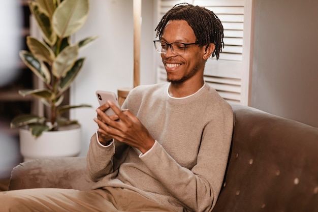 Man using modern smartphone device while on sofa at home