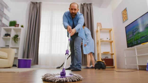 걸레를 사용하여 거실 바닥에서 먼지를 청소하는 남자.