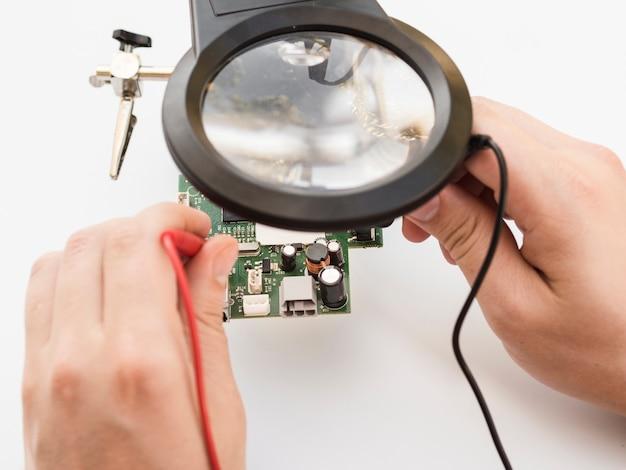 Человек с помощью мультиметра для проверки платы