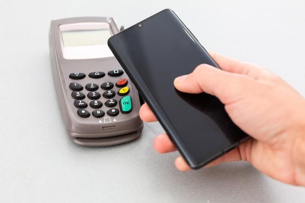 청구서를 지불하기 위해 스마트 폰에서 nfc 기술을 사용하는 남자