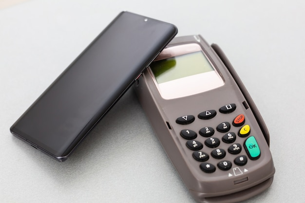Man using nfc technology on smart phone to pay bill