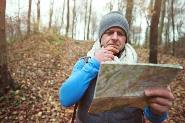 森の中で紙の地図を使用している男