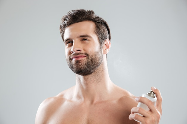 Man using perfume isolated