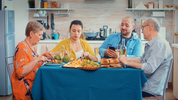 Man using phone during dinner showing some pictures to her mother. multi generation, four people, two happy couples talking and eating during a gourmet meal, enjoying time at home.