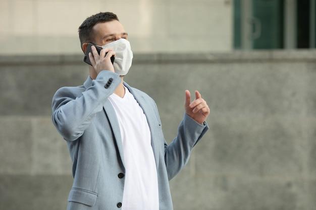 通りのフェイスマスクで電話を使用している男