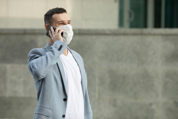 Человек, использующий телефон в маске для лица на улице