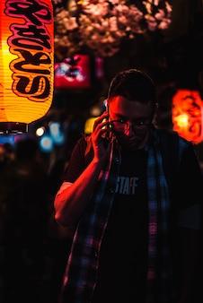 Uomo che utilizza il telefono stando in piedi durante la notte