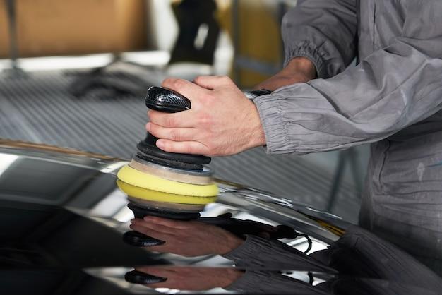 Человек с помощью полировщика для полировки черного кузова автомобиля в мастерской