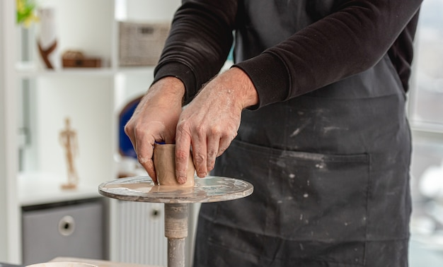 Man using pottery wheel for molding cup from clay at workshop
