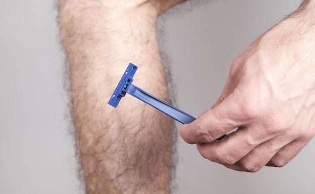 면도기를 사용하여 다리의 머리카락을 제거하는 남성.