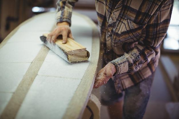 Человек, использующий шлифовальный блок в мастерской