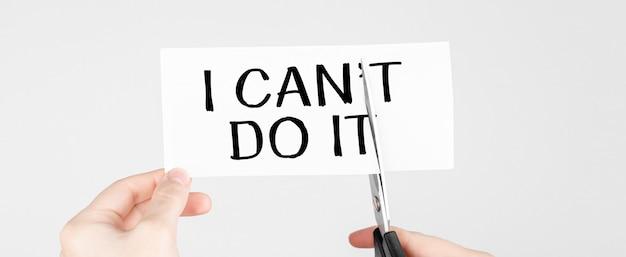 はさみを使って単語を削除する男は読めない私はそれを行うことができます自己信念、前向きな姿勢とモチベーションの概念