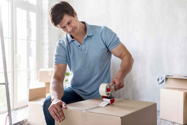 Man using scotch tape on box to secure it for moving out
