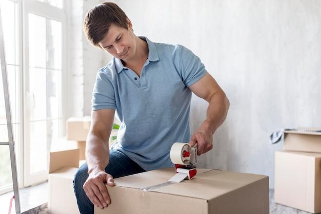 Человек, используя скотч на коробке, чтобы закрепить ее перед выездом