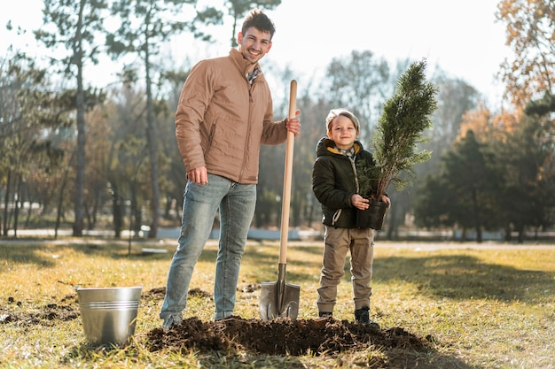 Man using shovel to dig a hole for planting a tree while posing next to son