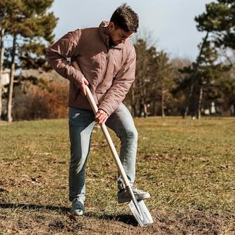 삽을 사용하여 나무를 심기 위해 구멍을 파는 남자