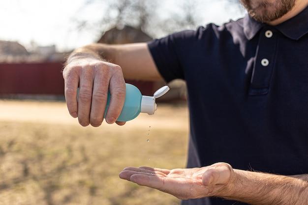 Man using small portable bottle of antibacterial sanitizer