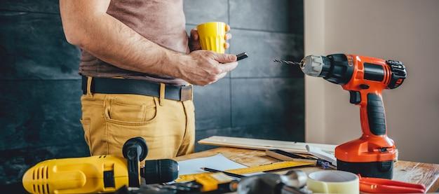 Человек с помощью смарт-телефона и держа чашку кофе