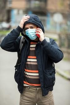 얼굴 마스크를 쓰고 도시에서 스마트 폰을 사용하는 사람