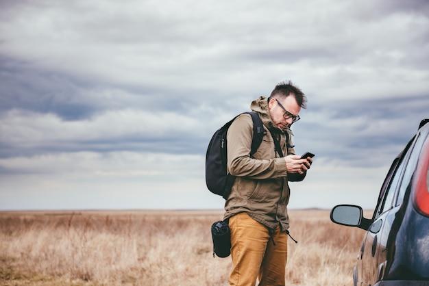 Человек с помощью смарт-телефона на открытом воздухе