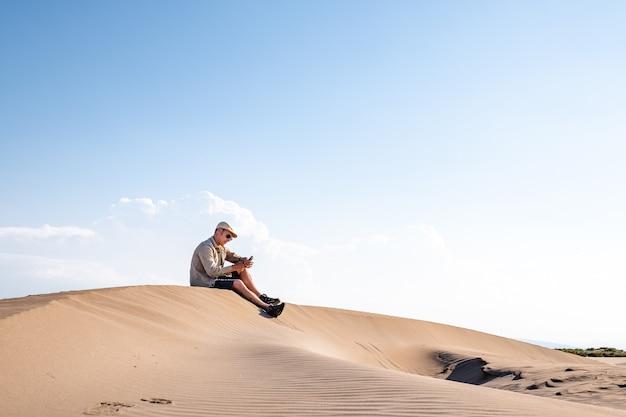 砂漠の砂丘だけでインターネット接続のスマートフォンを使用している男