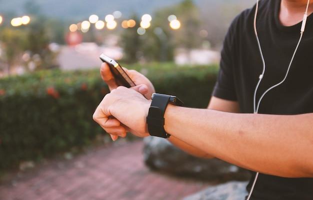 スマートな時計アプリを使用している人。ソーシャルメディアの概念。