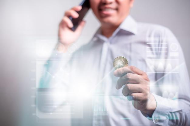 스마트폰을 사용하고 투명한 화면에 그래프가 있는 비트코인을 들고 있는 남자. 디지털 화폐 투자 개념, 블록체인 전송.