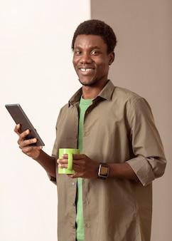 スマートフォンを使用してマグカップを持っている男