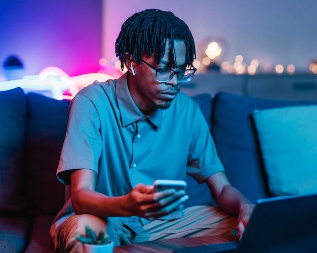 집에서 소파에있는 동안 스마트 폰 및 노트북을 사용하는 남자