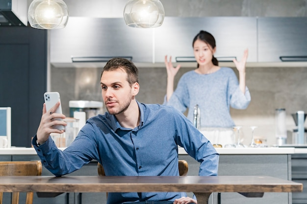 A man  using  smartphone and an angry woman