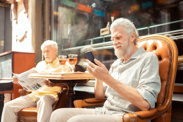 Man using smartphone. bearded aged man using smartphone while having lunch with friend outside