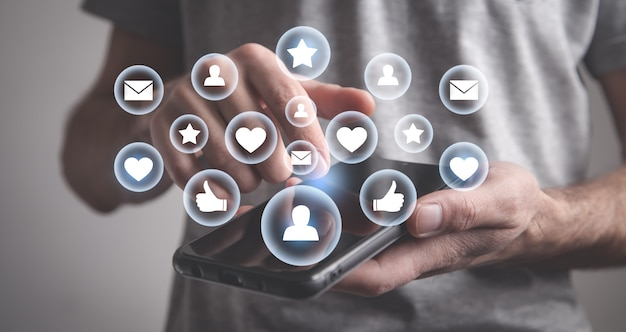 スマートフォンを使用している男性インターネットビジネステクノロジーに連絡する