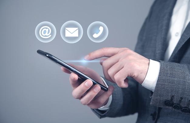 スマートフォンを使用している男性。連絡先。ソーシャルメディア。インターネット