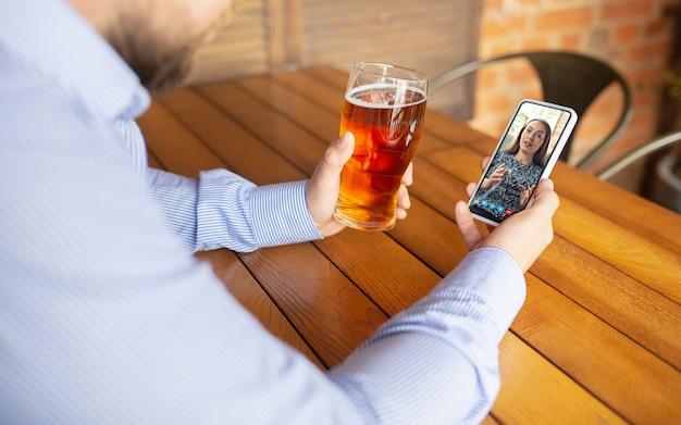 맥주를 마시는 동안 videocall에 스마트 폰을 사용하는 남자