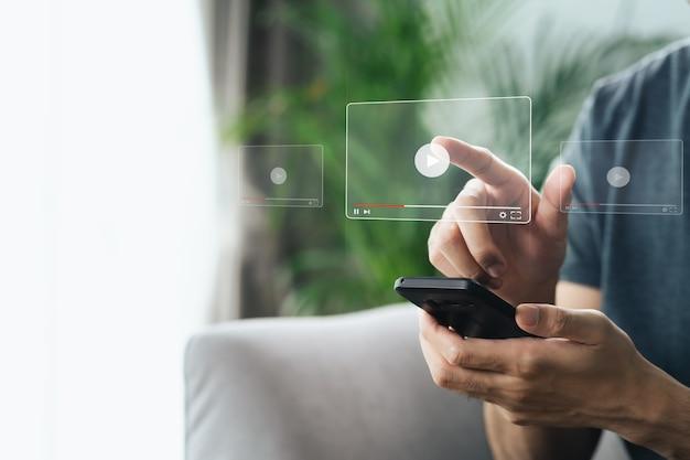 인터넷, 온라인 스트리밍, 온라인 수업, 콘텐츠 제작자에서 비디오를 보기 위해 스마트폰을 사용하는 남자