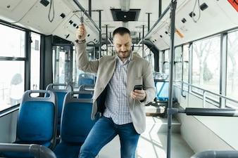 バスでスマートフォンを使っている男