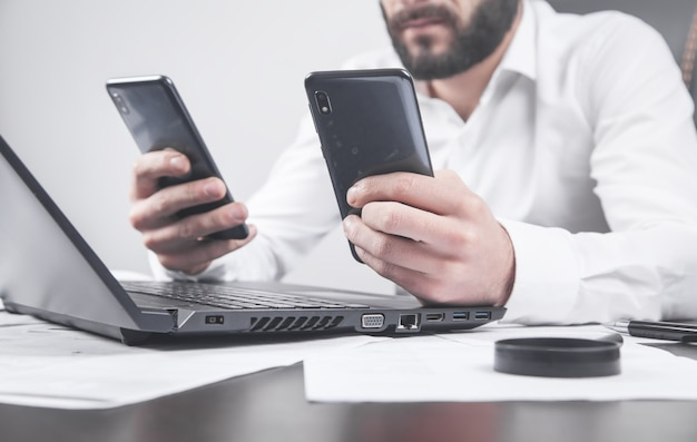 Человек с помощью смартфона. современный офисный стол. технологии