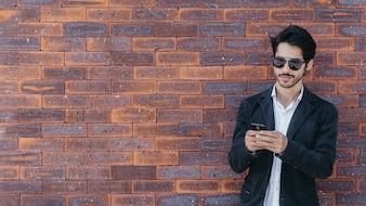Man using smartphone near brick wall