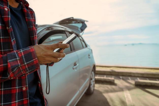 Человек, использующий смартфон, стоящий рядом с машиной и на берегу моря
