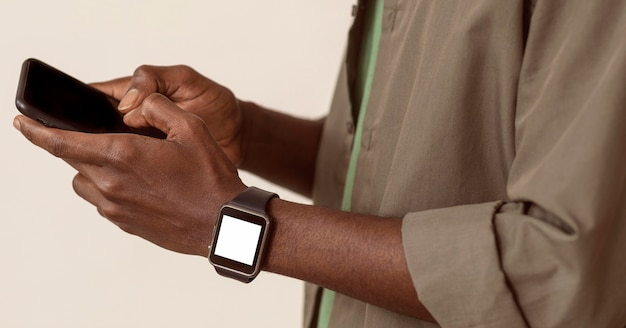 Man using smartphone and wearing smart watch
