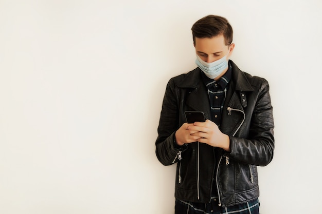 Man using smartphone while wearing surgical mask near white wall.