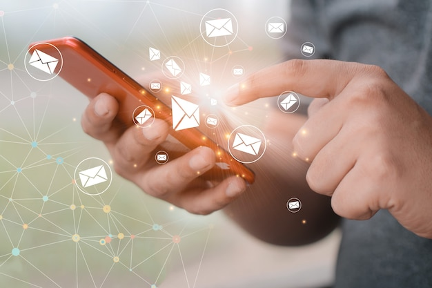 Man using smartphone with inbox e-mail icon.